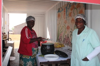 Caregivers cooking porridge for children from the community