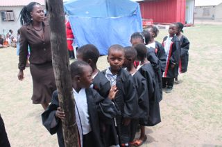 Children lining up to graduate in their smart gowns